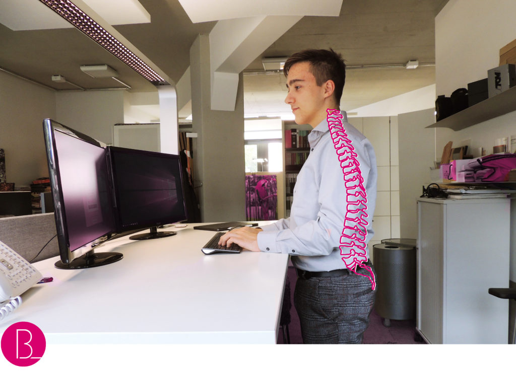 junge steht am Schreibtisch Büroland