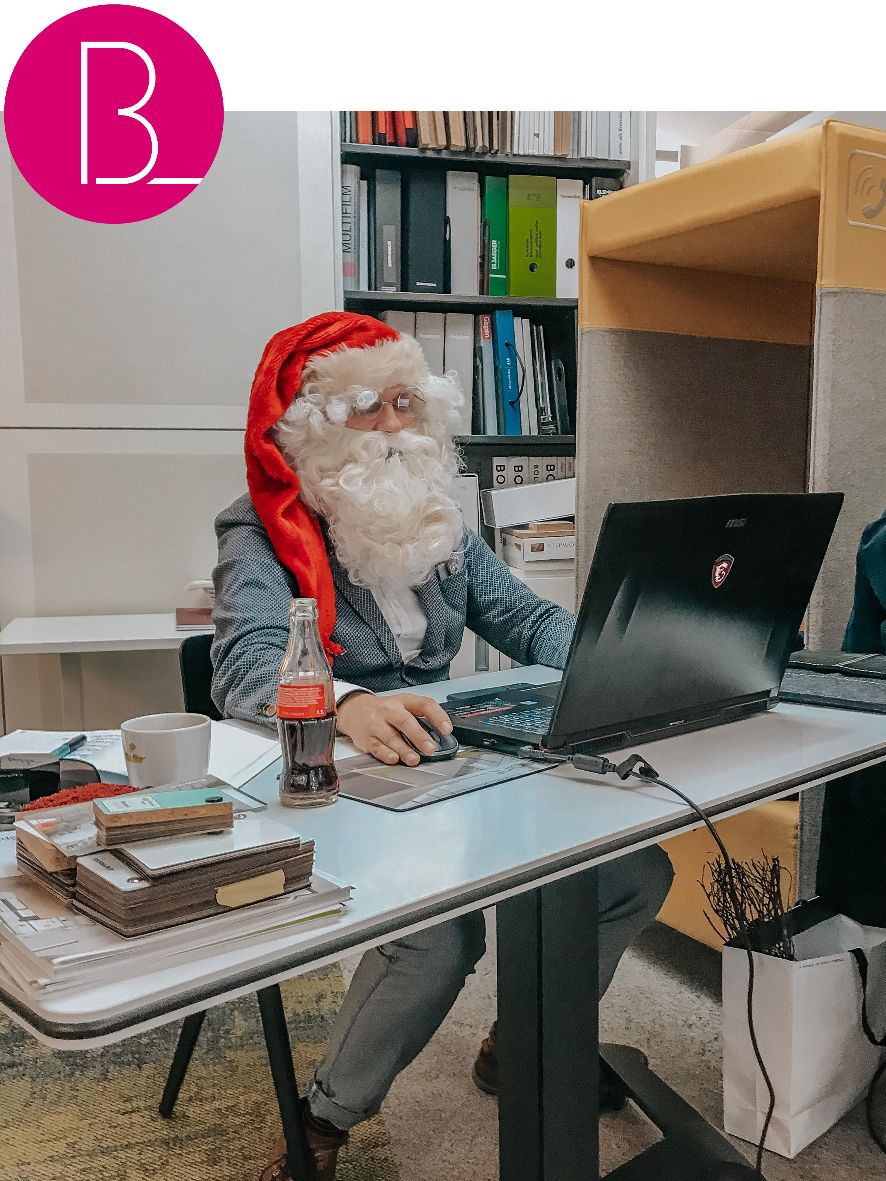 Büroland Kollege im Weihnachtsmann Kostüm sitzt am höhenverstellbaren Schreibtisch